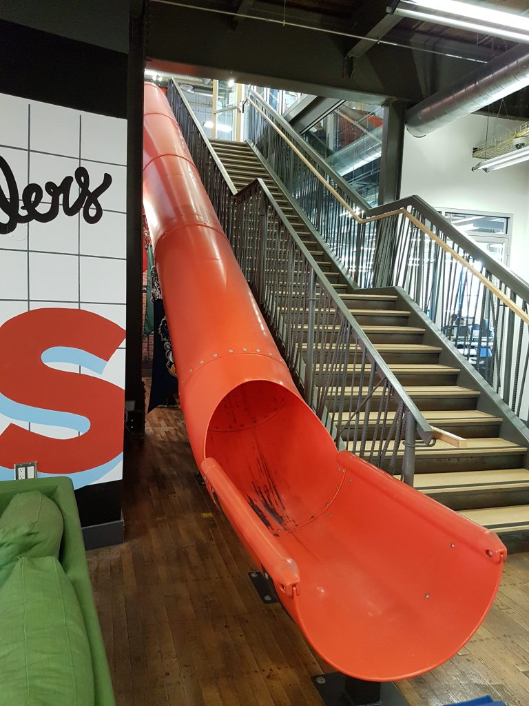 A big orange slide next to a staircase at Communitech's offices.
