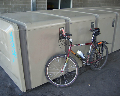 A bicycle in front of a row of secure boxes