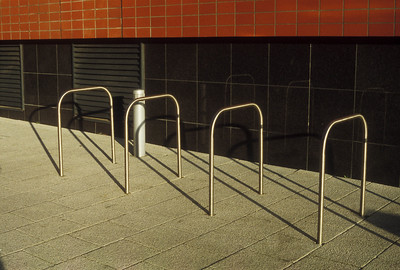 Four rectangular metal bars unconnected to each other with lots of space between for bike parking