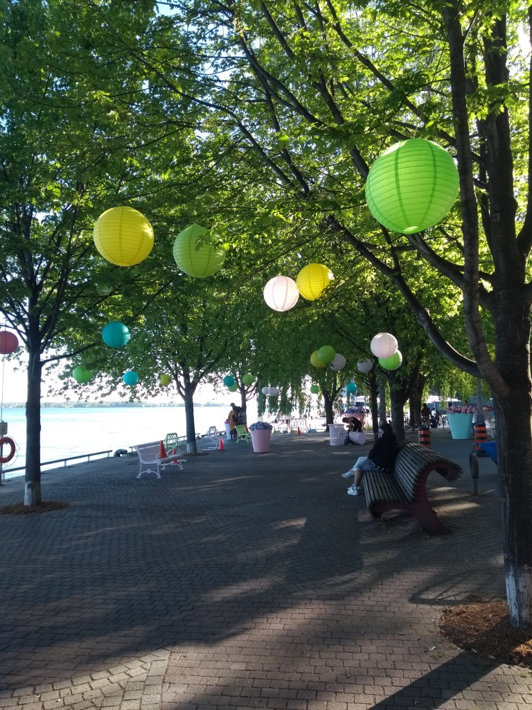 Colourful paper lanterns in trees above a pedestrian walkway along the waterfront at Sugar Beach
