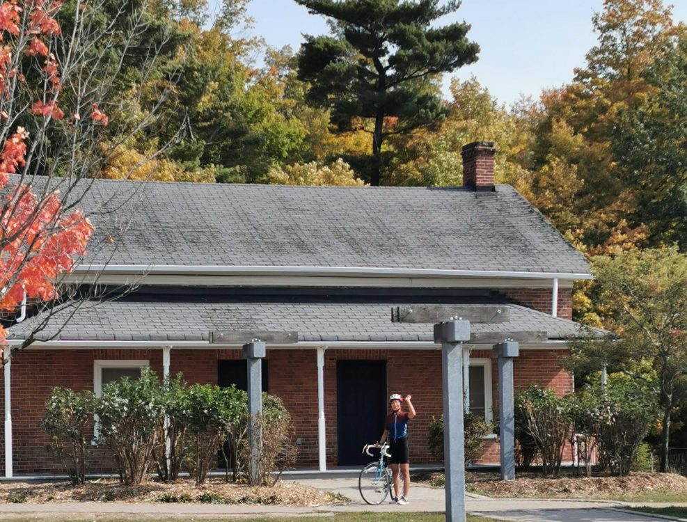 Person standing with bicycle in front of historic house